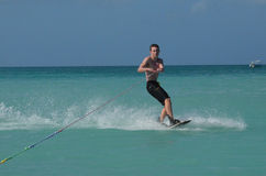 Young Guy Carving on a Wakeboard in Aruba. Young man carving and turning on a wakeboard Stock Photo