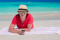Young guy with cellphone on tropical white beach Royalty Free Stock Photography