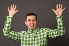 Young guy in a checkered shirt. On a gray background Stock Image