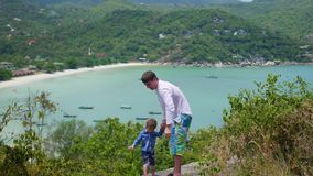 A young guy with child playing against the background of sea and mountains stock footage
