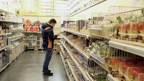 Young guy chooses electrical goods in store. Young guy chooses electrical goods in a store stock video footage