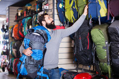 Young guy choosing new backpack in shop stock image