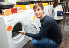 Young guy choosing new laundry machine. Happy young guy choosing new laundry machine in supermarket stock images