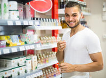 Young guy choosing perfume in the shop Royalty Free Stock Photos