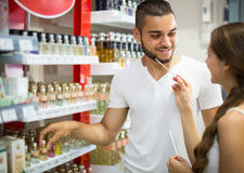 Young guy choosing perfume in the shop Stock Photos