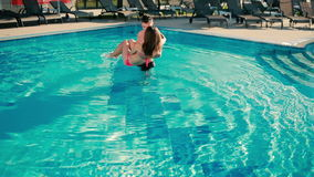 Young guy circling his girlfriend in his hands in swimming pool stock video