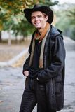 A young guy in a coat and hat stands and smiles in the park. stock images