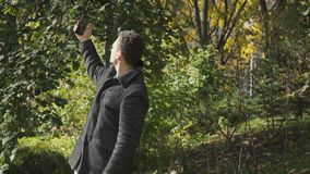 Young guy in coat searches a signal of network on his smartphone in park stock footage
