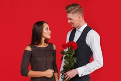 The guy is going to give the girl a bouquet of roses on a red background royalty free stock image