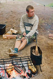 The young guy-cook at a campfire Stock Photography