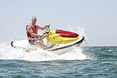 Young guy cruising on the atlantic ocean. On a jet ski Stock Photography