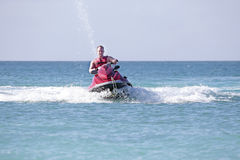 Young guy cruising on the caribbean sea. On a jet ski Stock Images