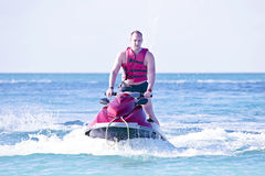 Young guy cruising on a jet ski. Young guy cruising in the caribbean sea on a jet ski Stock Image