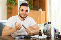 Young guy cutting nails Royalty Free Stock Photo