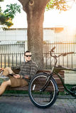 Young Guy Cyclist Resting On Bench And Using Tablet Communication Connection Digital Devices Technology Concept. Handsome young guy in sunglasses resting on Stock Photo