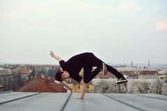Young guy dancing break dance on the roof Royalty Free Stock Photo