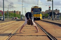Young guy dancing breakdance on tramlines in the city. Czech Republic Royalty Free Stock Image