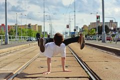Young guy dancing breakdance on tramlines in the city Stock Photo