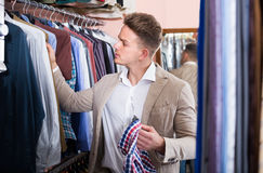 Young guy deciding on new shirt in men's cloths store Royalty Free Stock Photography