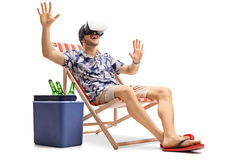 Young guy in a deck chair using a VR headset Stock Photo