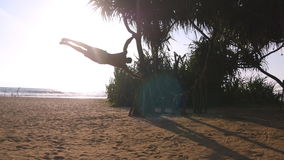 Young guy demonstrates human flag at sea beach. Athletic man doing gymnastics elements on palm tree at exotic ocean Stock Images