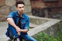 Young guy in denim, walks on the street, sit Stock Photos