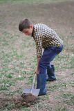 The boy is digging the earth in a park autumn. Person digging in garden Royalty Free Stock Image