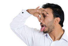 A young guy with disgust on face, pinching nose as something  stinks badly Stock Image
