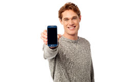 Young guy displaying brand new cellphone Royalty Free Stock Photo