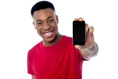 Young guy displaying brand new cellphone. Brand new cellphone is out for sale, buy now Stock Photo