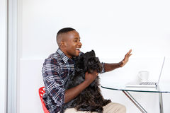 Young guy with a dog waving while video chatting on laptop Stock Images