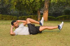 Young guy doing abs exercise. In a park Royalty Free Stock Photography