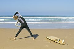 Young guy doing exercises. Before going to surf Stock Photos