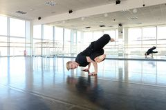 Young guy doing physical exercises in black sport suit. Male sportsman preparing body for loads and doing stretching. Blonde boy wears black suit and sitting on Royalty Free Stock Images