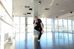 Young guy doing physical exercises in black sport suit. Male sportsman preparing body for loads and doing stretching. Blonde boy wears black suit and sitting on Royalty Free Stock Photography