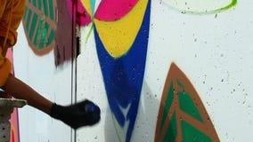 Young guy drawing graffiti on wall Stock Photo