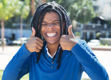 Young guy with dreadlocks showing both thumbs in the city Stock Photo