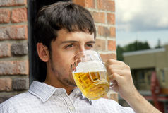 Young guy drinking beer. Portrait of a sad young man drinking beer out of glass bok on pub's outdoor terrace Stock Images