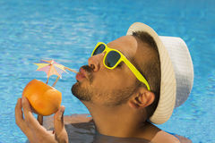 Young guy drinking fresh grapefruit juice in the swimming pool Royalty Free Stock Images