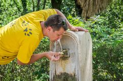 A young guy drinks water, quenching thirst from an antique drinking fountain, the nose of Rome in the shape of a bronze wolf, a ho Stock Photo