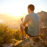 Young guy eating a protein bar at sunrise on a hike. Rearview shot of a young guy on a nature trail pausing to eat a protein bar while watching the sunrise Royalty Free Stock Images