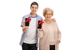 Young guy and elderly woman showing phones with red ribbon Stock Photography