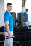 Young guy is engaged with a dumbbell Royalty Free Stock Photos