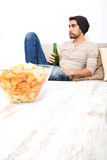 Young guy enjoying beer and chips in the living room Royalty Free Stock Photos