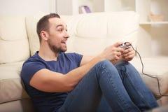 Young guy enjoying computer game, playing with joystick Stock Image