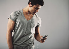 Young guy enjoying listening music on smartphone Royalty Free Stock Images