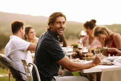 Young guy enjoying at outdoor party with friends. Handsome men having drinks with friends sitting by at dinner party. Young guy enjoying at outdoor party with royalty free stock photo