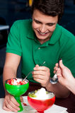 Young guy enjoying tempting dessert Royalty Free Stock Images