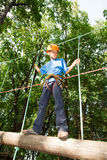 Guy with equipment climber moves on a balk. Young guy with equipment climber moves on a balk holding the ropes Royalty Free Stock Photography