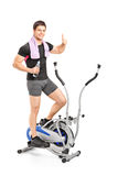 Young guy exercising on a cross trainer machine Stock Photo